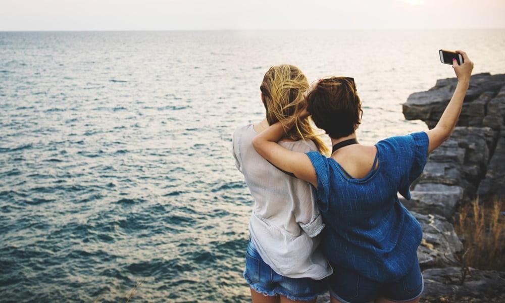 Gente usando el móvil frente al mar