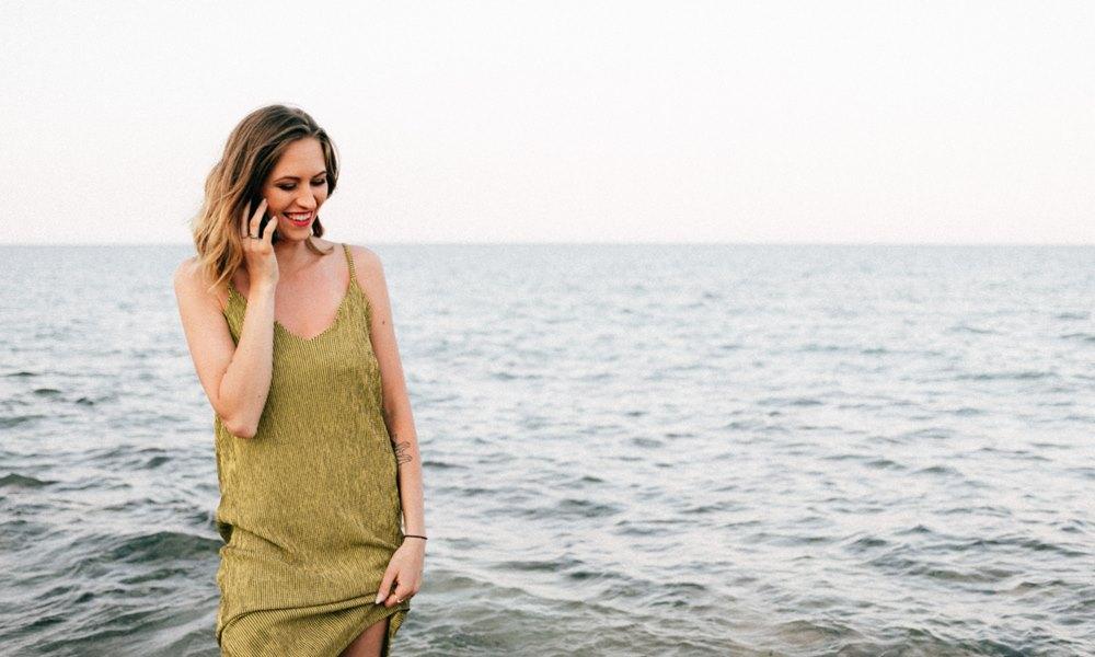 Mujer frente al mar hablando por el móvil