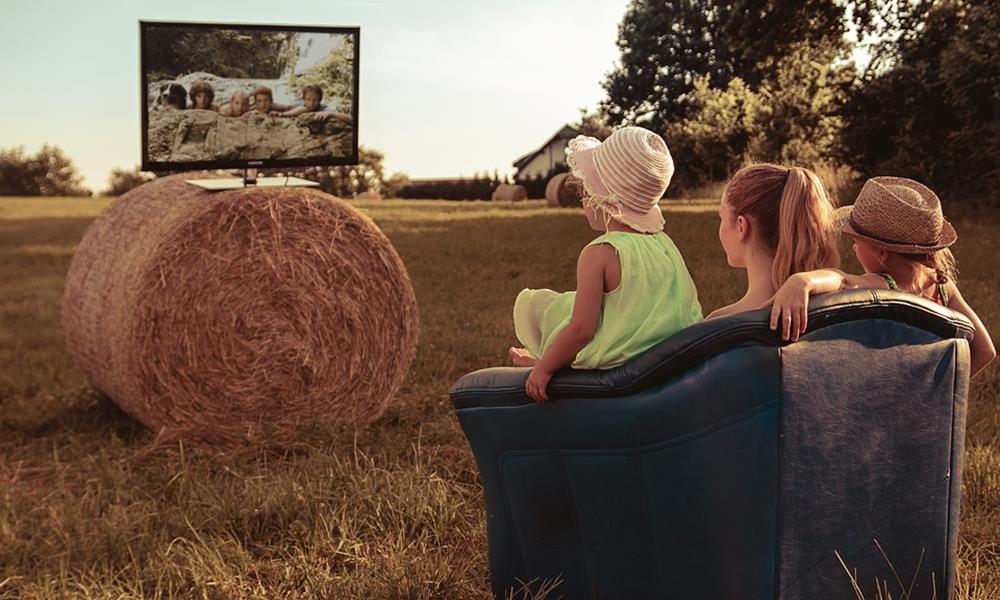 Familia viendo la tele al aire libre