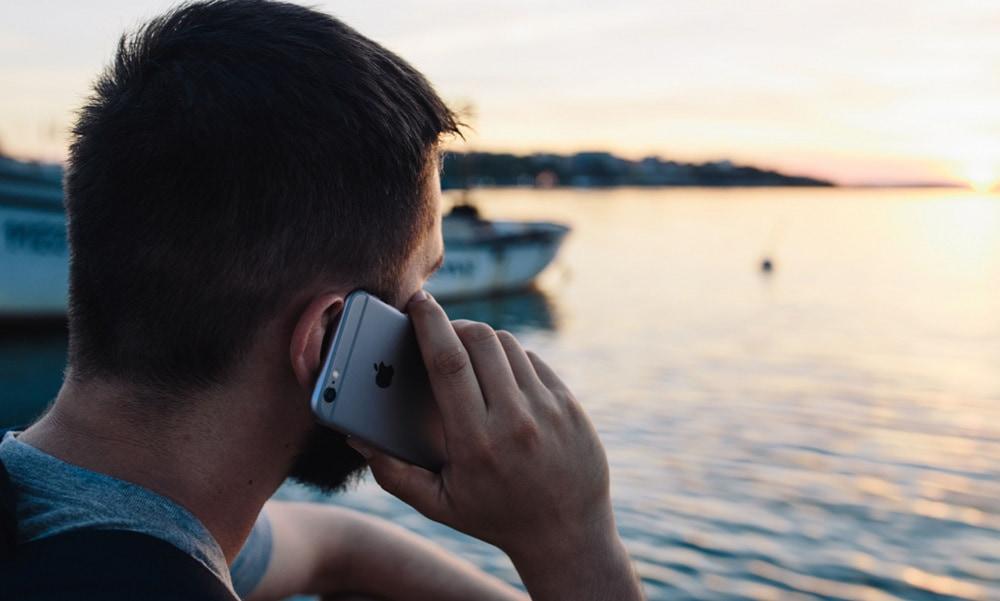 Hombre hablando por el móvil frente al mar