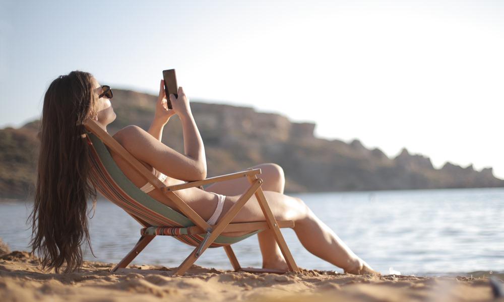 Chica en la playa disfrutando de su móvil