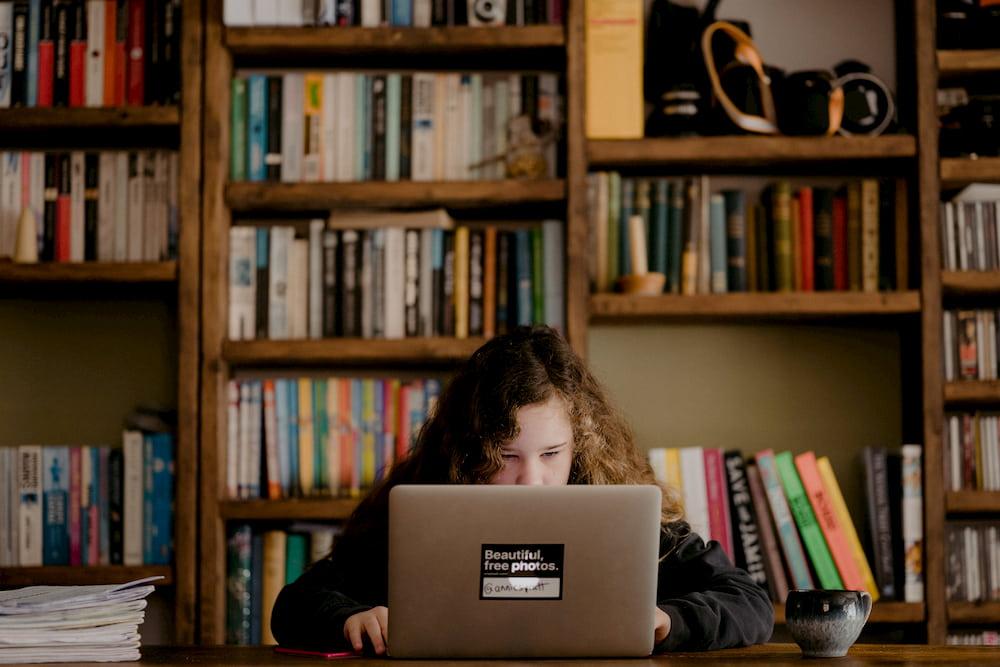 Niña navegando por internet en un despacho